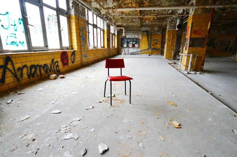 Empty red chair in abandoned building
