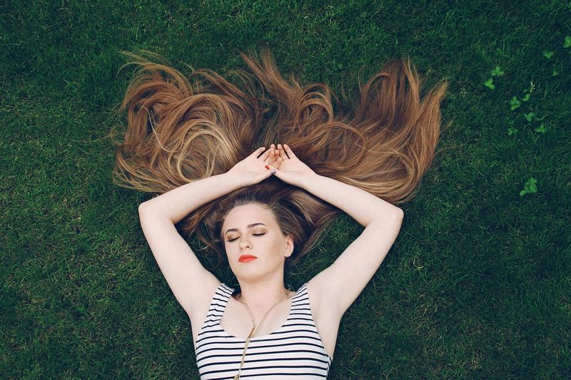 High Angle View Of Woman Relaxing On Grassy Field