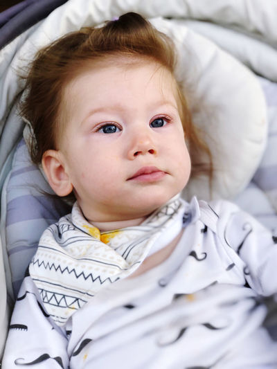 Close-up of cute baby relaxing on bed at home