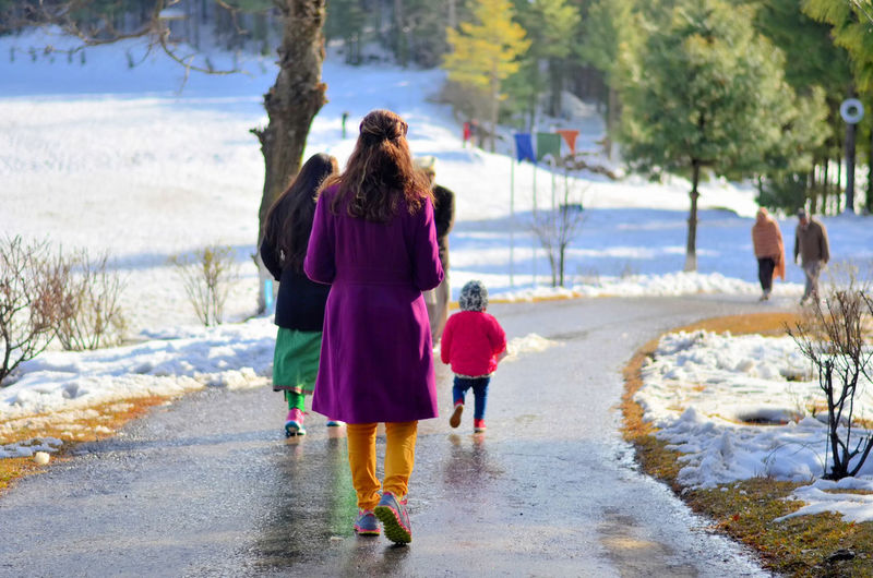Rear view of girls walking on snow covered landscape