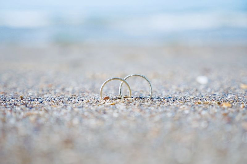 Selective Focus Beach Land Close-up No People Ring Jewelry Wedding Ring Day Sand Diamond - Gemstone Outdoors Still Life Wedding Wealth Personal Accessory Life Events Water Nature Surface Level