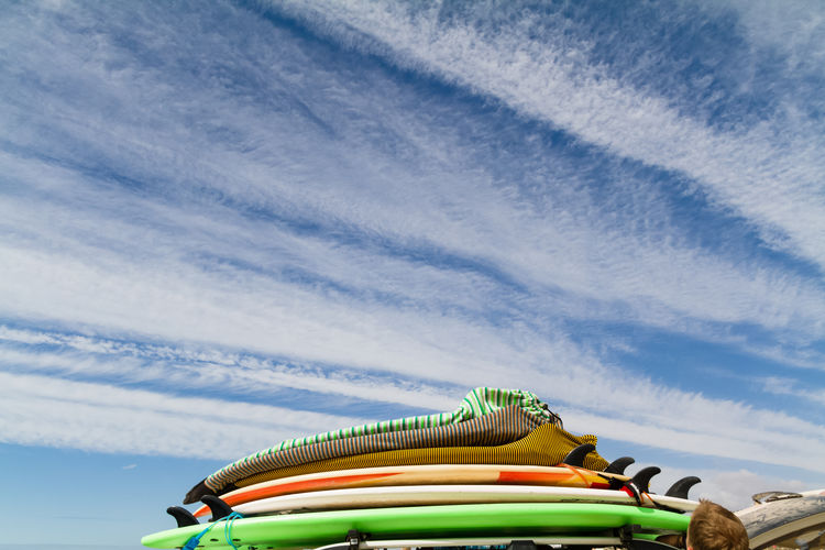 Stack Of Surfboards Against Cloudy Sky