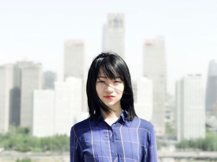 Portrait of young woman standing against cityscape