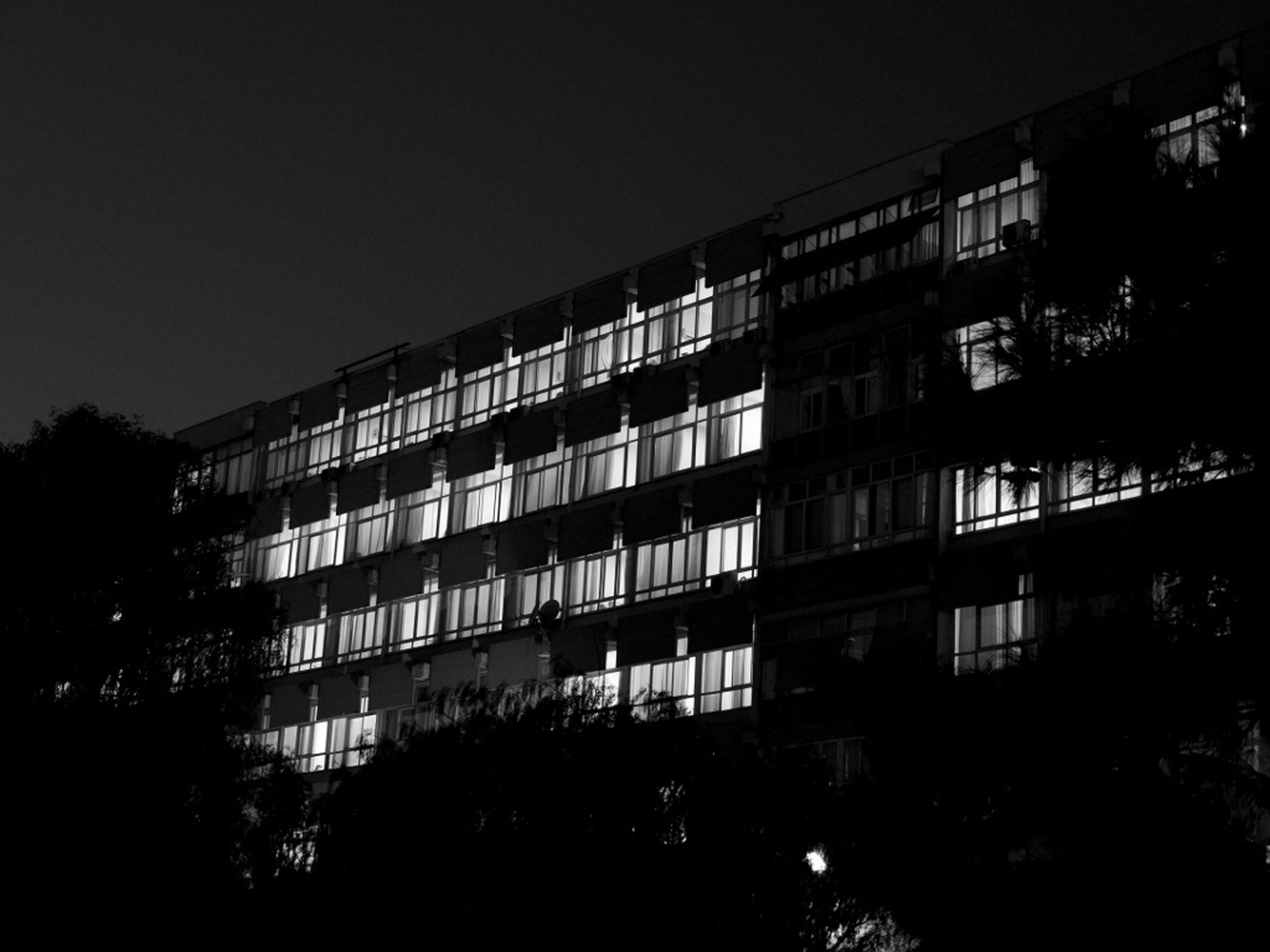 architecture, built structure, building exterior, low angle view, city, building, clear sky, residential building, window, night, residential structure, illuminated, tree, sky, outdoors, no people, exterior, city life, apartment, balcony