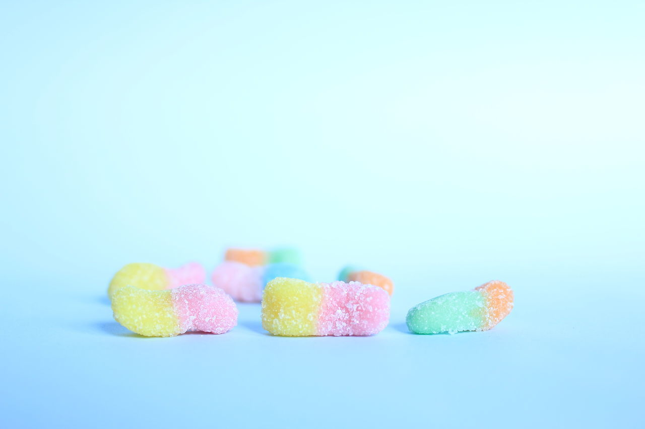 Close-Up Of Sugar Coated Candies On Blue Table