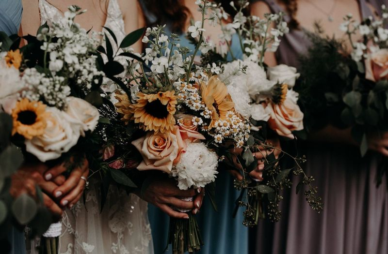 Midsection of bridesmaids holding bouquet