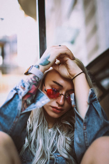 Portrait of a woman in red glasses and a denim jacket