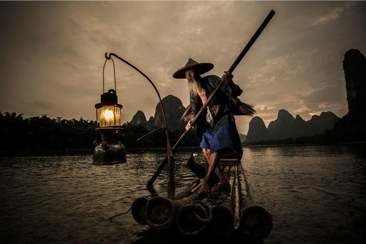 Senior chinese fisherman at sunset
