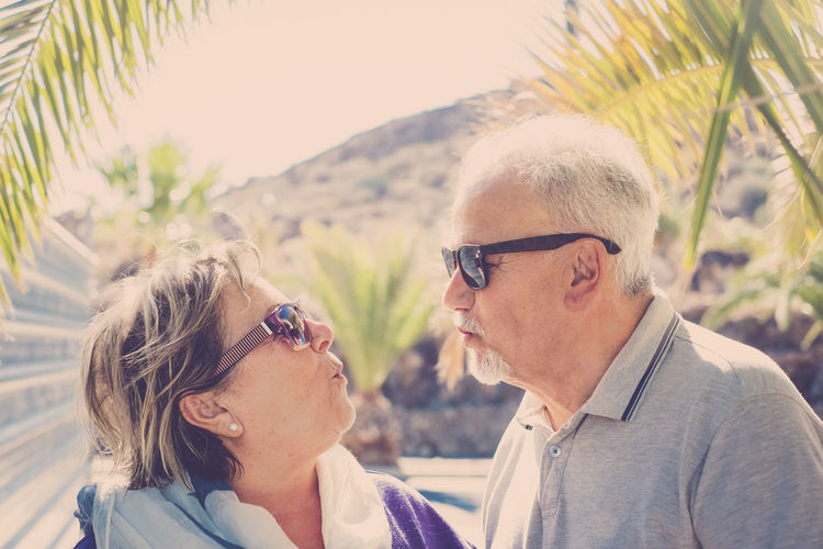 elderly senior couple with sunglasses walking outdoor in the sun Confidence  Gray Beard Gray Hair Standing Bonding Casual Clothing Day Elderly Funny Faces Happiness Kissing Lifestyles Looking Each Other Love Outdoors Palm Trees Real People Serenity In Nature Sun Sunglasses Togetherness Two People
