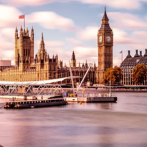 Pier on thames river by big ben and houses of parliament against sky