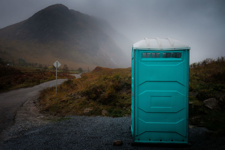 Portable toilet in front of a mountain in Glen Etive, Scotland Mist, Toilet, WC, Perspectives On Nature Beauty In Nature Communication Day Grass Green Color Guidance Landscape Mountain Nature No People Outdoors Road Road Sign Scenics Sky