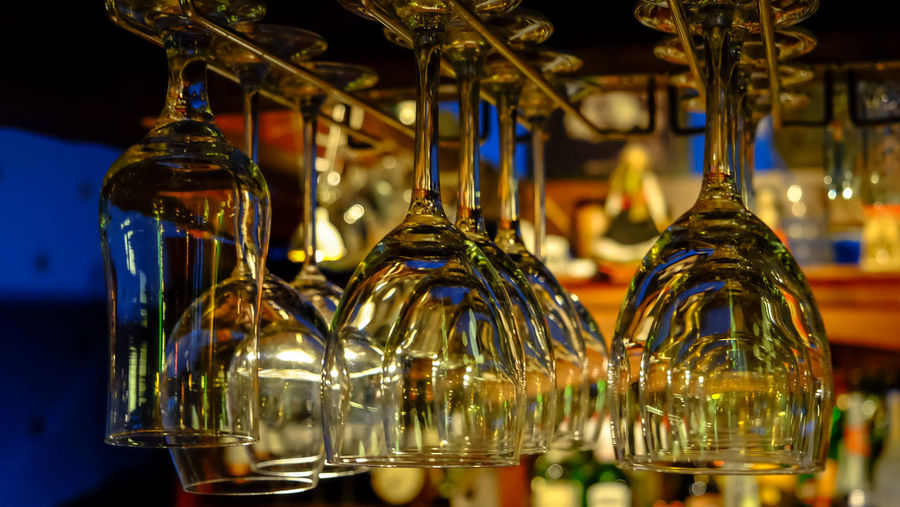 Alcohol Bar - Drink Establishment Bar Counter Bottle Business Close-up Container Decoration Focus On Foreground Food And Drink Glass Glass - Material Hanging Illuminated Indoors  Lighting Equipment No People Selective Focus Still Life Transparent Upside Down Wine Wineglass