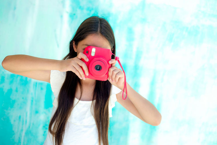 Teenage girl photographing with instant camera against wall