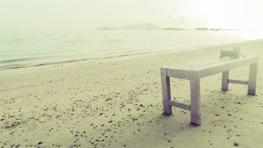 The camera is placed on a table by the sea Placed The Cameraman A Table By The Sea Beach Beauty In Nature Day Horizon Horizon Over Water Idyllic Land Nature No People Non-urban Scene Outdoors Sand Scenics - Nature Sea Seat Sky The Camera Tranquil Scene Tranquility Water Wood Wood - Material