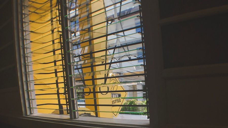 Low angle view of yellow glass window in building