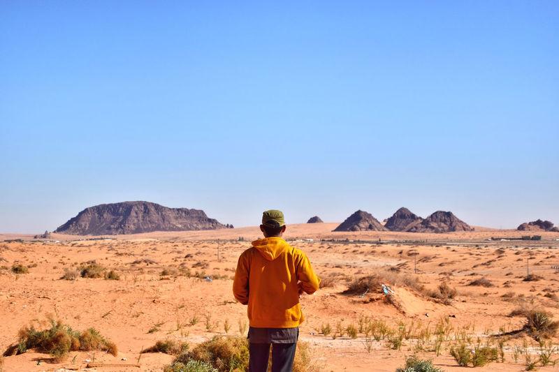 Rear view of man standing on desert
