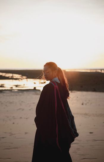 Side view of woman standing at beach against sky during sunset