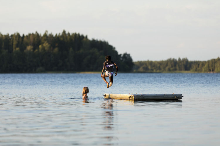 Men in lake against sky