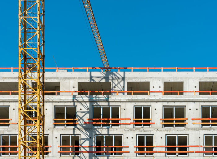 Low angle view of crane against building against clear blue sky