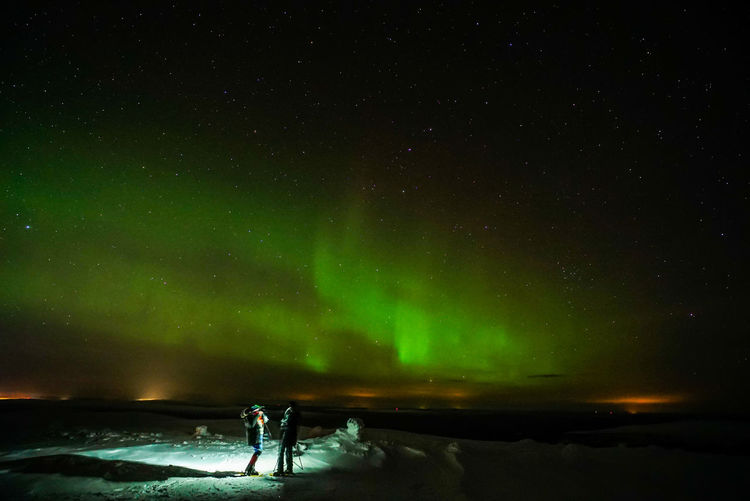 Hikers looking at northern lights while standing on snow covered field at night