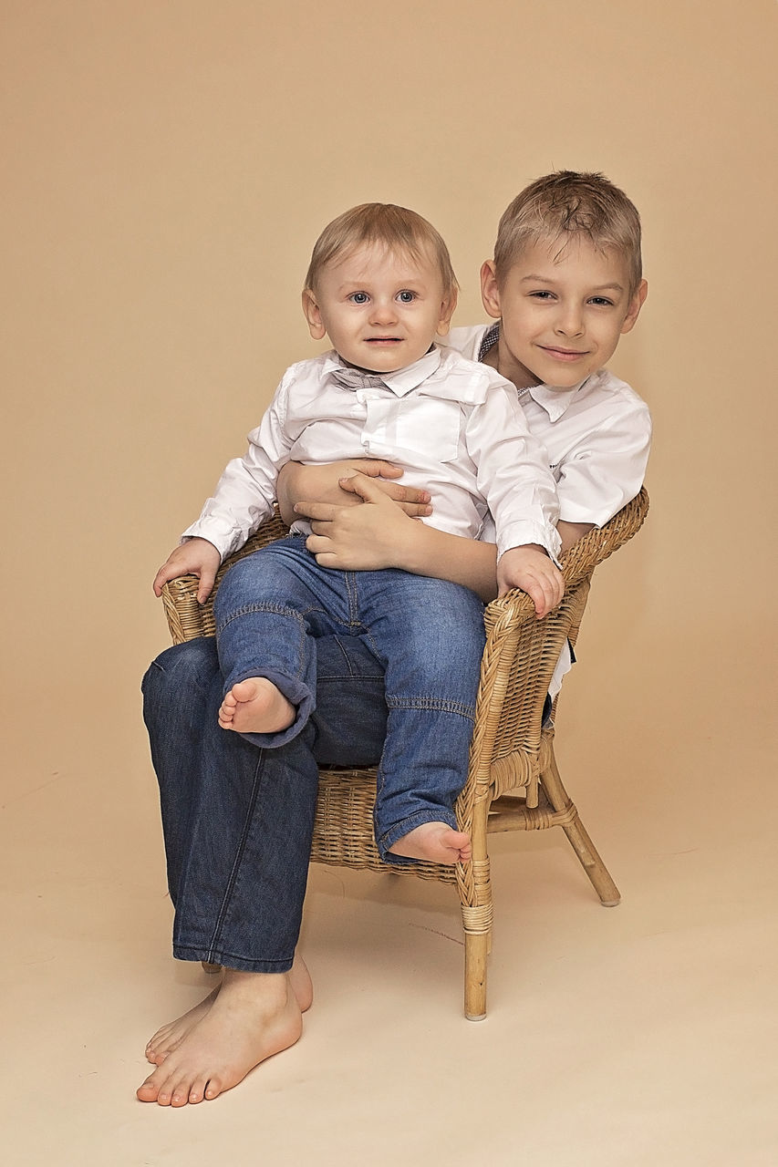 Portrait Of Brother Sitting On Wicker Chair Against Brown Background