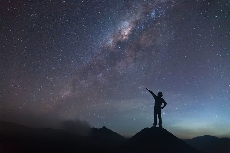 Astronomy Beauty In Nature Full Length Galaxy Leisure Activity Lifestyles Low Angle View Men Milky Way Mountain Nature Night One Person Outdoors Real People Scenics Silhouette Sky Space Standing Star - Space Star Field Starry Tranquil Scene Tranquility