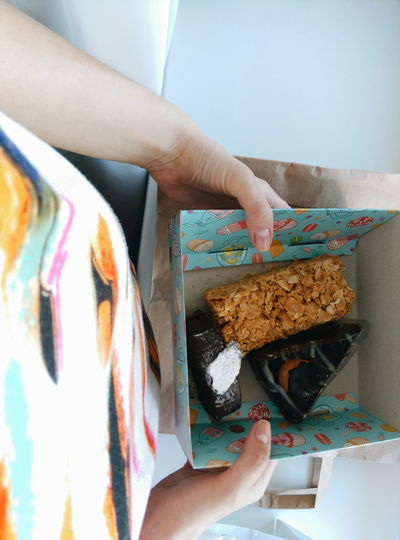 Midsection Of Woman Holding Pastries In Box