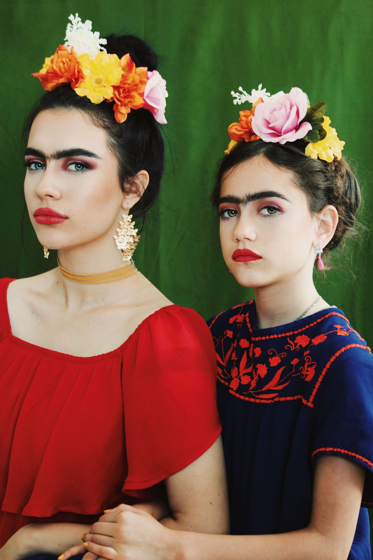 Portrait of women wearing flowers on hair against curtain