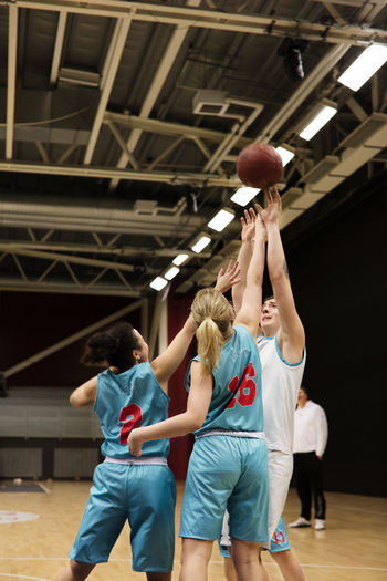 Rear view of two people playing basketball