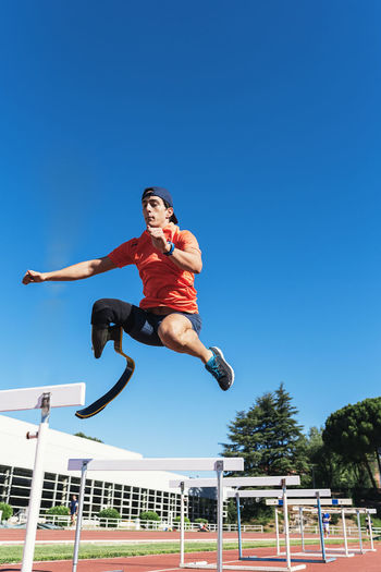 Low angle view of athlete with prosthetic leg jumping above railings at running track