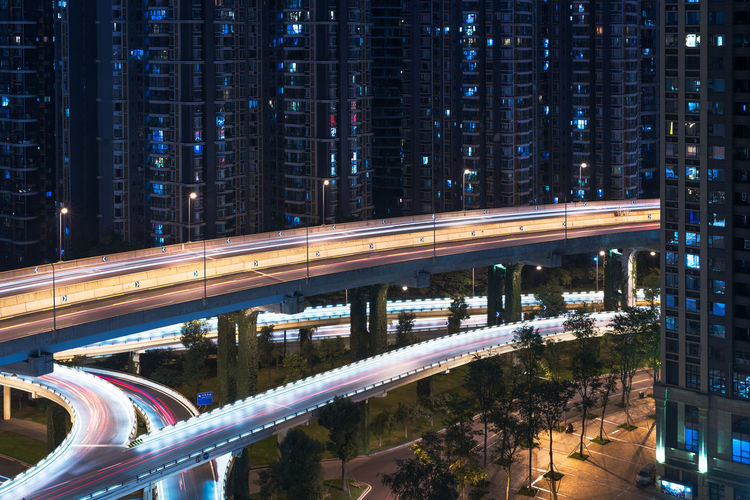 Aerial road crossing residential Buildings at night in Chengdu - China Architecture Blurred Motion Bridge - Man Made Structure Building Exterior Built Structure City City Life Connection Elevated Road High Angle View Highway Illuminated Light Trail Long Exposure Modern Motion Night Outdoors Road Skyscraper Speed Street Street Light Traffic Transportation