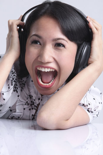 malaysia malay woman listening music using headphones Earphones Females Happiness Headphones Music ShoutOut Woman Beautiful Woman Casual Clothing Enjoy Front View Headshot Leisure Activity Lifestyles Listen Malay Malaysia Mouth Open One Person Portrait Relaxation Studio Shot White Background Young Adult Young Women