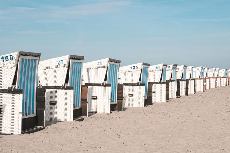 Hooded Beach Chairs On Sand Against Sky