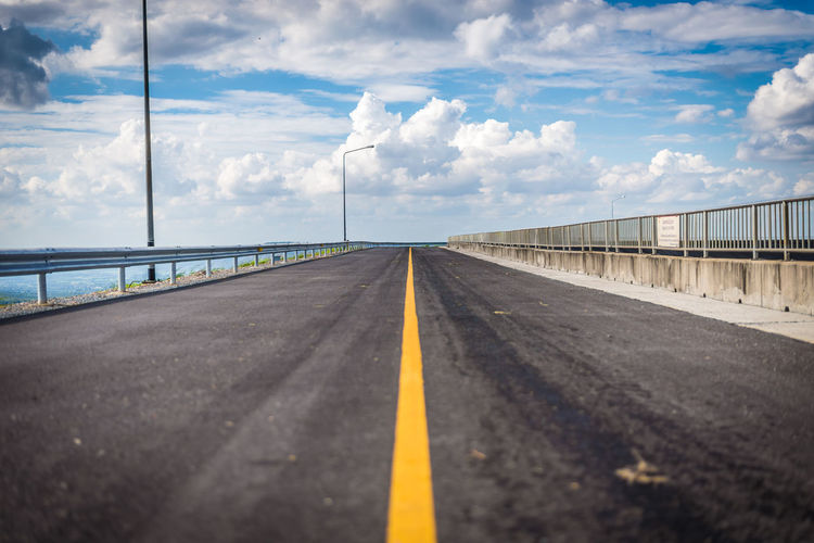 Cloud - Sky The Way Forward Road Marking Transportation Direction Road Marking Sky Symbol Sign Diminishing Perspective Connection Day Nature vanishing point Railing Asphalt No People Dividing Line Outdoors Surface Level Long