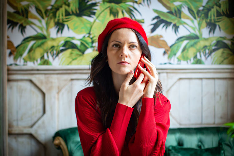 Red One Person Clothing Young Adult Front View Real People Lifestyles Young Women Hat Looking Adult Beautiful Woman Leisure Activity Portrait Looking Away Beauty Focus On Foreground Waist Up Hairstyle Warm Clothing Contemplation Telephone Speaking On The Phone