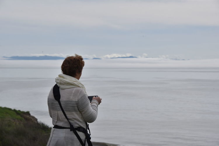 Rear view of woman photographing fog through smart phone against sky