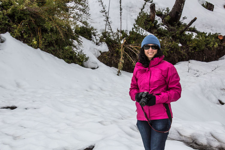 Full length portrait of woman standing on snow covered trees