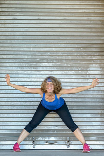 Portrait of woman stretching while standing against shutter