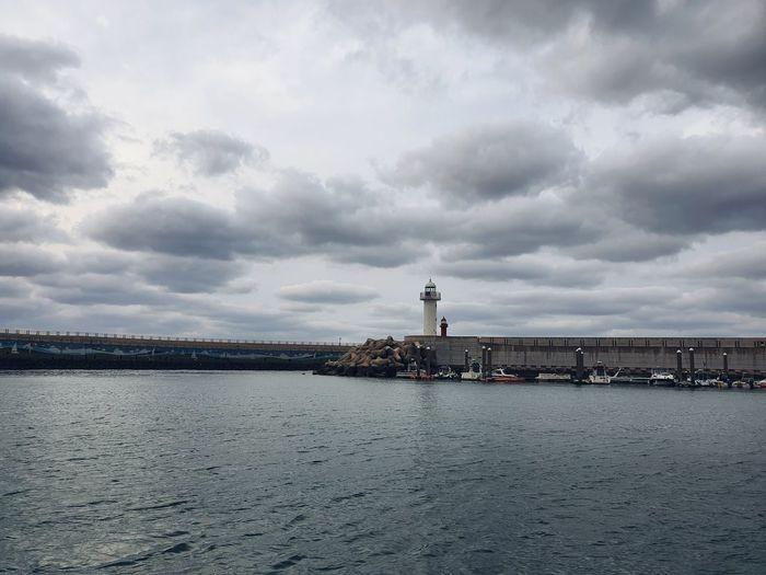 View of building by sea against cloudy sky
