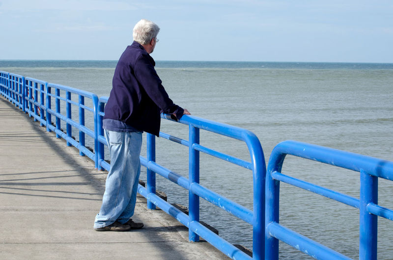 A senior male dressed in blue stand against a blue background and a blue railing. is he also feling blue? Contemplation Feeling Blue Lake Michigan USA Adult Beach Beauty In Nature Blue Day Depression - Sadness Full Length Horizon Over Water Leisure Activity Nature Older Male Outdoors People Railing Retirement Scenics Senior Adult Sky Standing Tranquil Scene Water This Is Aging Creative Space