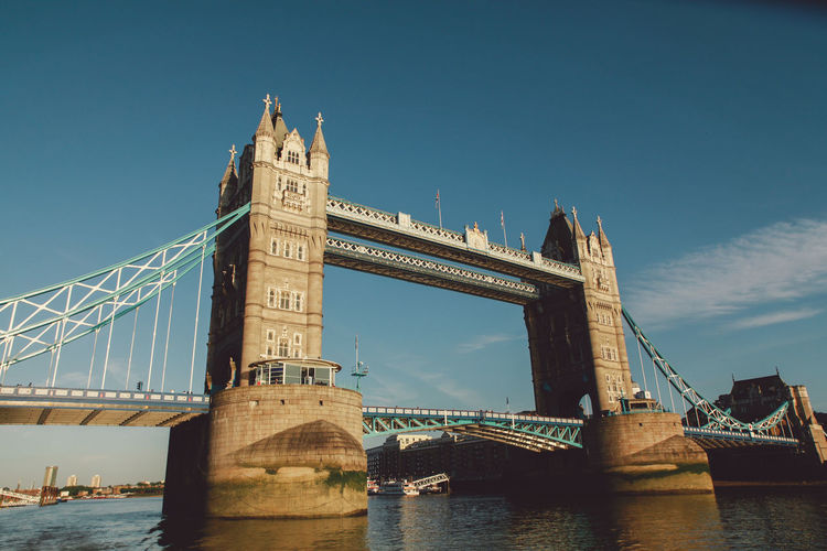 Low angle view of tower bridge over thames river against blue sky