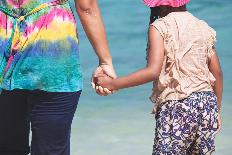 Midsection of woman and girl holding hands while standing in sea