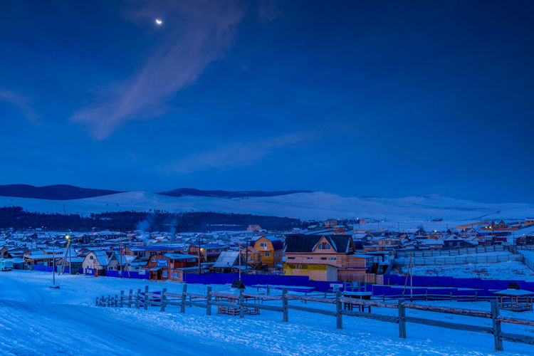 Scenic view of snow covered buildings against blue sky