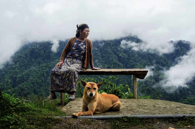 Senior Woman Sitting On Table By Dog On Mountain