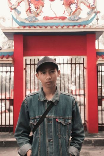 Portrait of a young man standing in front of a chinese temple