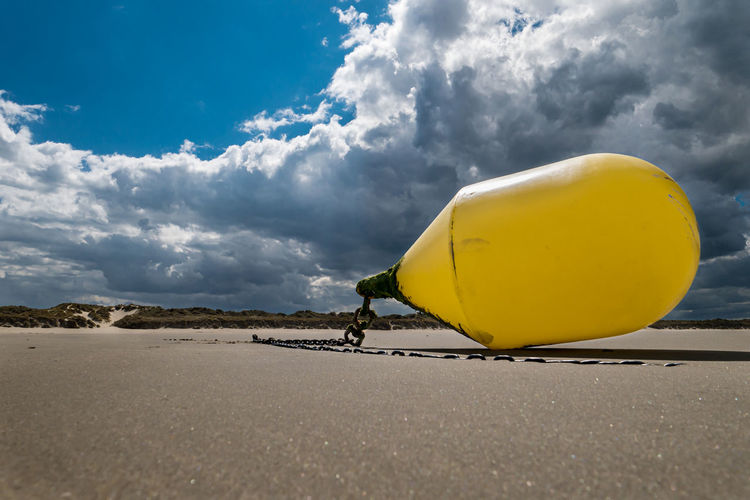 Low angle view of yellow umbrella on beach