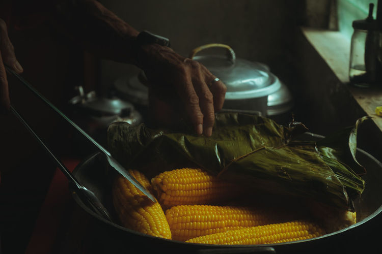 Close-up of person preparing food or corn