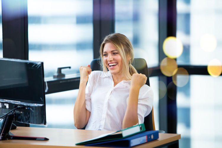 Happy young woman looking at computer in office