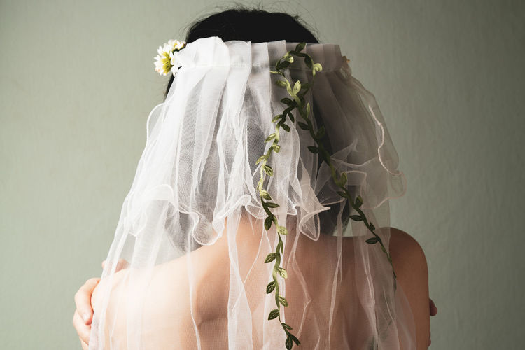 Rear view of bride with veil against wall