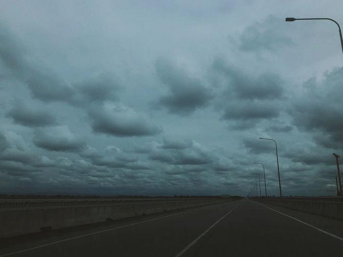 Street against cloudy sky at dusk